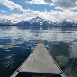 canoe on a lake in front of a mountain range