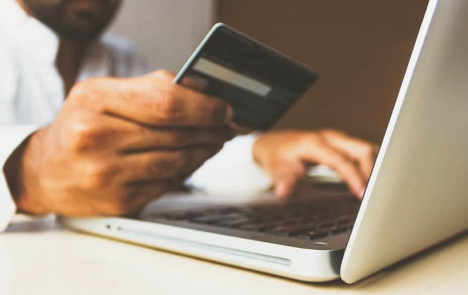Person, die eine Kreditkarte vor einen Laptop hält
