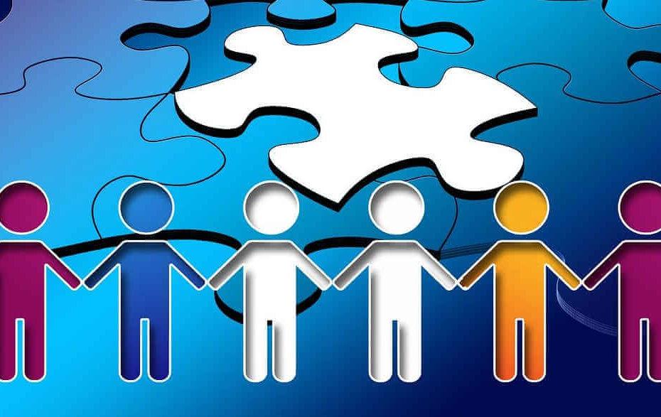 Mehrere Menschen halten sich vor einem Puzzle an den Händen