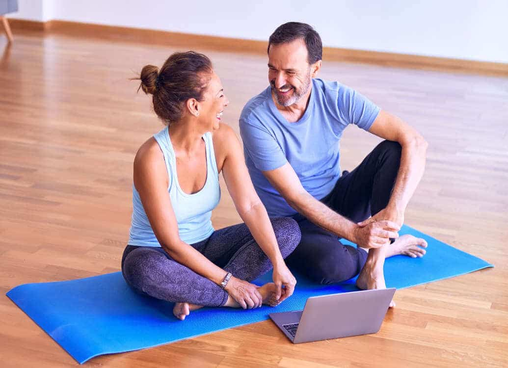 a man and a woman sitting on a yoga mat in front of a laptop
