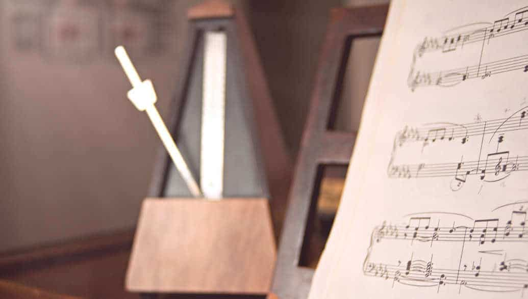 music notes and a metronome displayed on a table