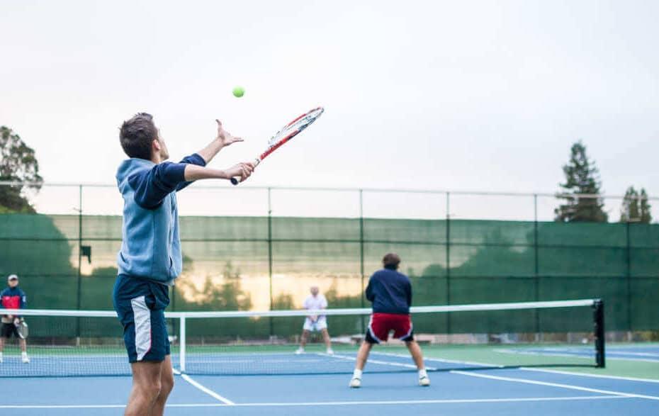 4 Männer spielen ein Doppel auf einem Tennisplatz.