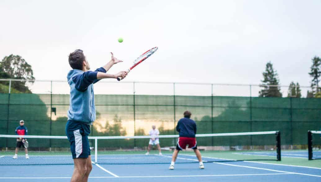 4 men playing doubles on a tennis court.